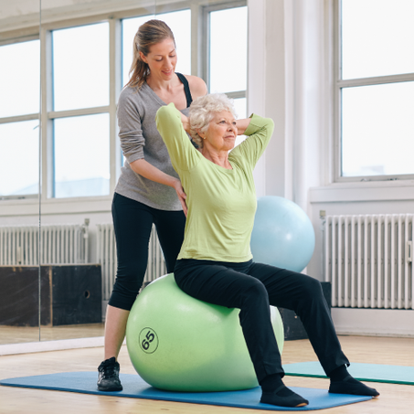 trainer and elderly client working her back